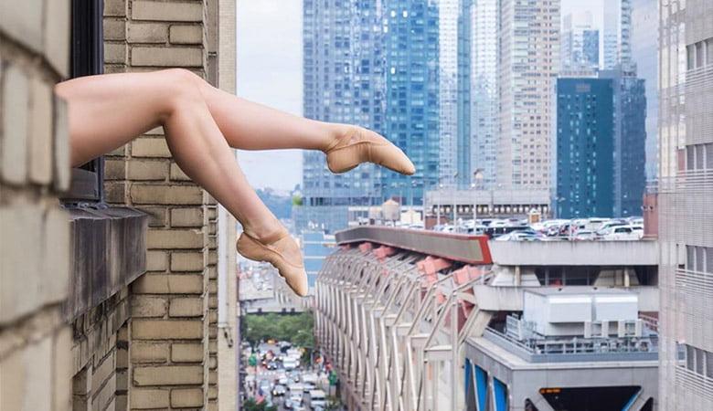 Bailarina em cima do prédio com os pés esticados